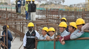 Seneglese and Chinese workers observe a ceremony at the national theater construction site financed by China on February 14, 2009 in Dakar, during a visit by Chinese president Hu Jintao and Senegalese president Abdoulaye Wade. AFP Photo / SEYLLOU (Photo credit should read SEYLLOU/AFP/Getty Images)